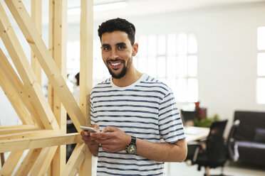 Portrait of smiling young man with cell phone in office - EBSF02545