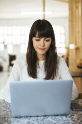 Portrait of young woman using laptop on table - EBSF02551