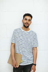 Portrait of smiling young man with clipboard at brick wall - EBSF02554