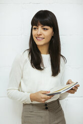 Portrait of smiling young woman with notebook at brick wall - EBSF02560