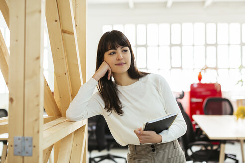Smiling young woman with notebook in office - EBSF02563