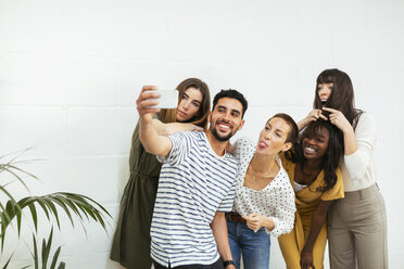 Playful colleagues standing at brick wall taking a selfie - EBSF02566