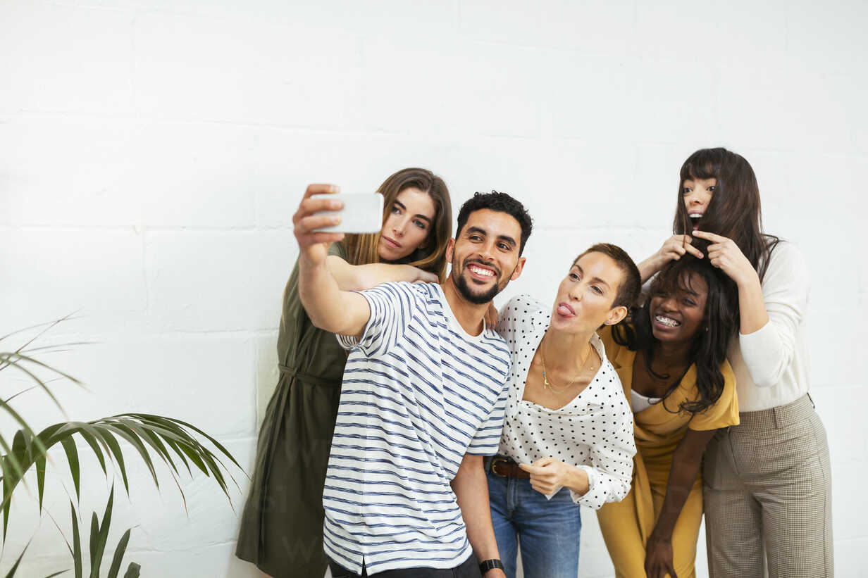 Playful colleagues standing at brick wall taking a selfie - EBSF02566 - Bonninstudio/Westend61