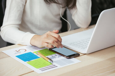 Close-up of woman with document, cell phone and laptop at desk in office - EBSF02572