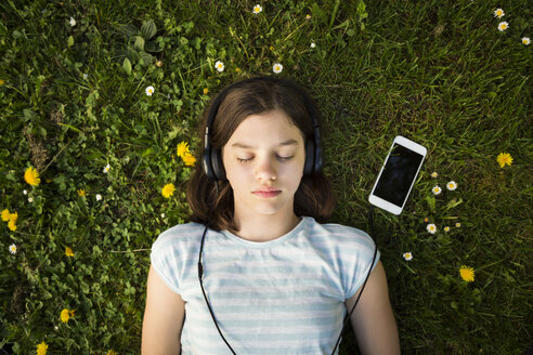 Portrait of girl lying on meadow listening music with headphones and smartphone - LVF06939