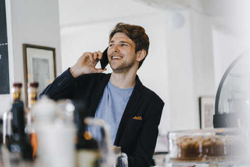 Smiling man in a cafe talking on cell phone - KNSF03850