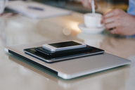 Stack of mobile devices and man with coffee - KNSF03856