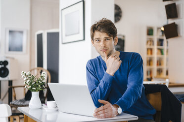 Portrait of man in a cafe sitting at table with laptop - KNSF03865