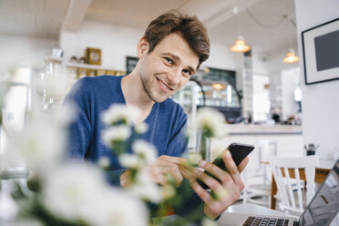 Portrait of smiling man in a cafe with cell phone and laptop - KNSF03874