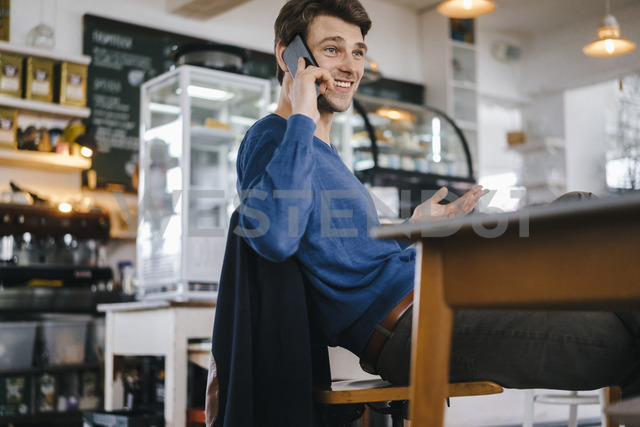Smiling man in a cafe on cell phone - KNSF03877 - Kniel Synnatzschke/Westend61