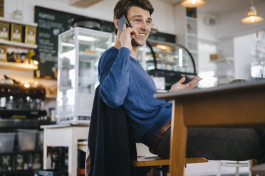 Smiling man in a cafe on cell phone - KNSF03877