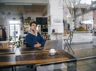 Man sitting at table in a cafe with laptop - KNSF03880