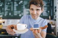 Smiling man in a cafe offering cup of coffee and holding miniature laptop model - KNSF03892