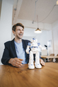 Laughing man with robot on table - KNSF03898