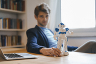 Man sitting at table with robot - KNSF03901
