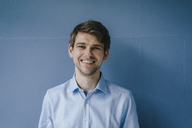 Portrait of smiling man in front of blue wall - KNSF03904