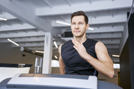 Portrait of man running on treadmill at gym - BSZF00309