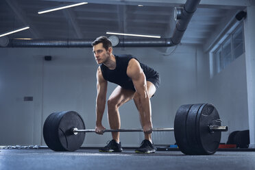 Man doing barbell exercise at gym during weight lifting workout - BSZF00318