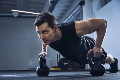 Man doing pushups on kettlebells at gym - BSZF00321