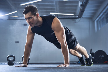 Athletic man doing pushups exercise at gym - BSZF00324