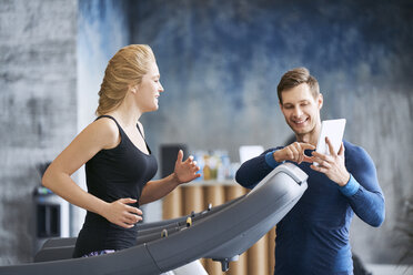 Woman running on treadmill with personal trainer at gym - BSZF00330