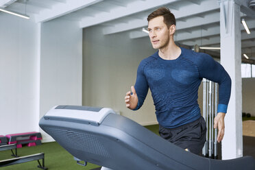 Man running on treadmill at gym - BSZF00333