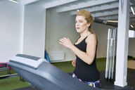 Woman running on treadmill at gym - BSZF00336