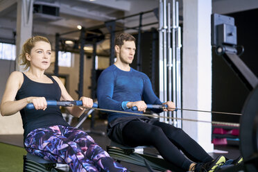 Man and woman at gym exercising together on rowing machines - BSZF00339