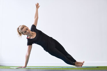 Woman doing side plank yoga exercise in studio - BSZF00345