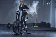 Athletic woman doing air bike workout at gym - BSZF00348