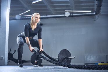 Athletic woman exercising with battle ropes at gym - BSZF00351