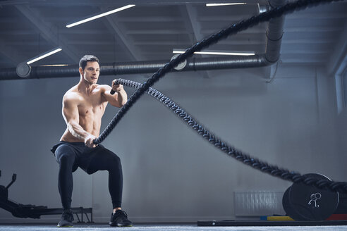 Athletic man exercising with battle ropes at gym - BSZF00354
