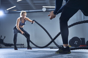 Athletic woman doing battlerope exercise with personal trainer at gym - BSZF00357