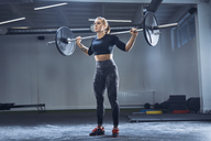 Woman practicing barbell squat at gym - BSZF00363