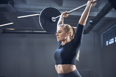 Woman doing push press exercise at gym - BSZF00366