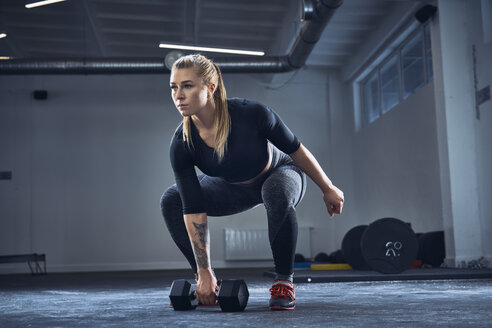 Woman doing dumbbell exercise at gym - BSZF00369