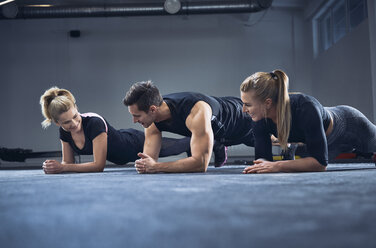 Three people doing plank exercise at gym - BSZF00372
