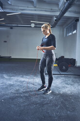 Woman adjusting jumping rope before exercise at gym - BSZF00375