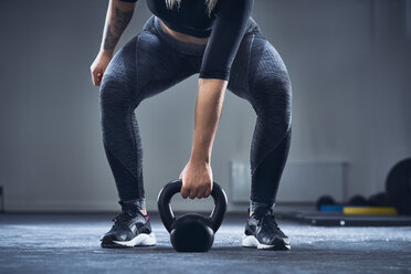 Close-up of athletic woman exercising with kettlebell at gym - BSZF00378
