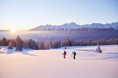 Austria, Tyrol, couple snowshoeing at sunrise - CVF00405