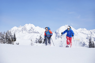 Austria, Tyrol, snowshoe hikers running through snow - CVF00429
