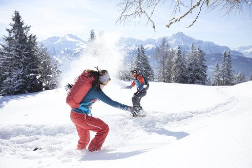 Austria, Tyrol, couple having fun in the snow - CVF00435
