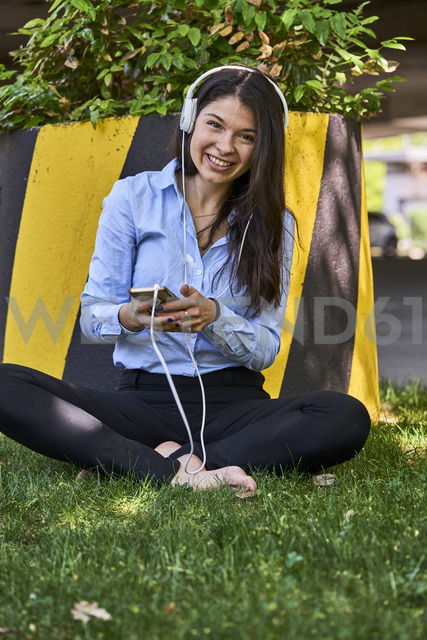 Portrait of smiling woman sitting barefoot on a meadow listening music with headphones and cell phone - BEF00034 - Benjamin Egerland/Westend61