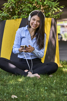 Portrait of smiling woman sitting barefoot on a meadow listening music with headphones and cell phone - BEF00034