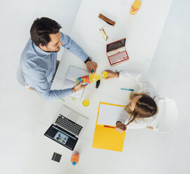Two business people at meeting table in office, top view - GUSF00751