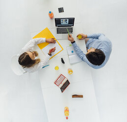 Two business people at meeting table in office, top view - GUSF00754