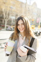 Spain, Barcelona, portrait of laughing young businesswoman with coffee to go - VABF01562