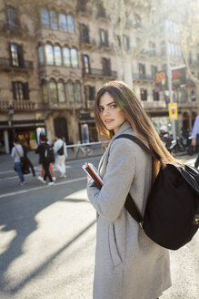 Spain, Barcelona, portrait of young woman with backpack standing at  street - VABF01565