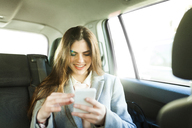 Portrait of smiling young businesswoman sitting on backseat of a car looking at cell phone - VABF01568