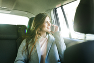 Smiling young businesswoman on the phone sitting on backseat of a car looking out of window - VABF01571